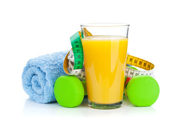 Two green dumbells, tape measure and orange juice. Fitness and h