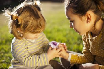 Niña dando flor a niña pequeña