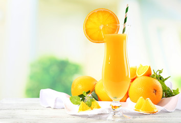Glass of orange juice with straw and slices