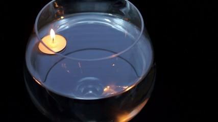 Floating burning candle in huge goblet