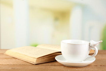 Cup and book on table, on bright background
