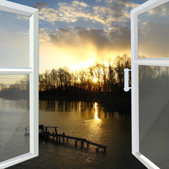 window opened to the river with sunset