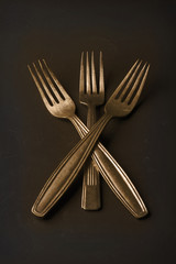 Simple still life of three gold vintage forks