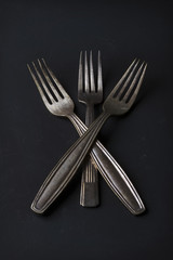 Conceptual still life of three vintage silver forks