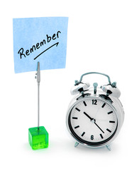 Remember text on blue notepaper and alarm clock