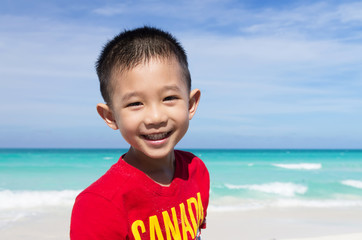 Cute little Asian boy standing on the beach all smiling wearing