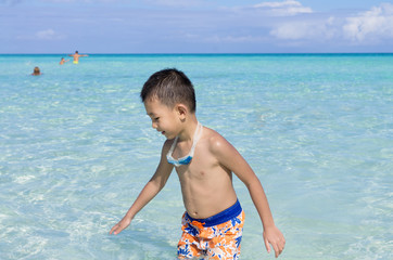 Cute little Asian boy playing with in blue turquoise water in Ca