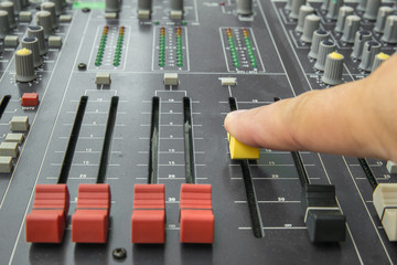 Finger pushing a mixing desk slide. Selective focus