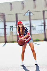 Sexy brunette woman playing basketball outdoor