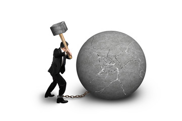 businessman holding hammer hitting cracked concrete ball isolate
