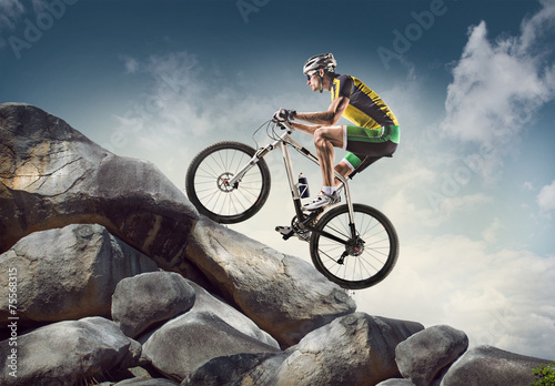 Zdjęcia na płótnie, fototapety, obrazy : Sport background. Cyclist climbing on a rock.