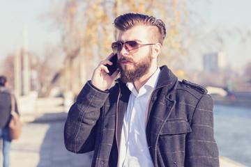 Handsome hipster  talking on mobile phone