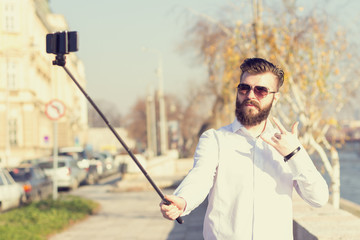 Hipster style bearded man taking selfie