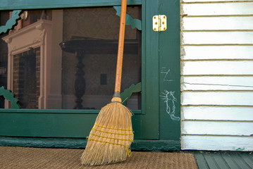 old broom with hobo sign on green door