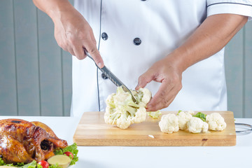 chef cutting cauliflower
