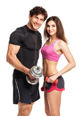 Athletic man and woman with dumbbells on the white