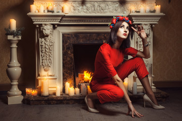 Girl in a red jumpsuit poses.