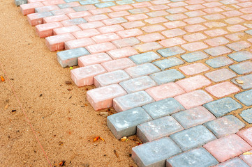 Colored brick paving stones in construction process