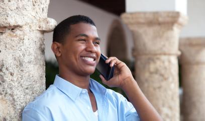 Lachender junger Mann aus Südamerika mit Handy
