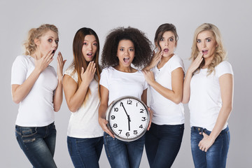 Multi ethnic shocked women with clock