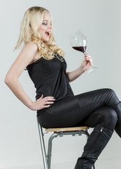 sitting young woman with a glass of red wine