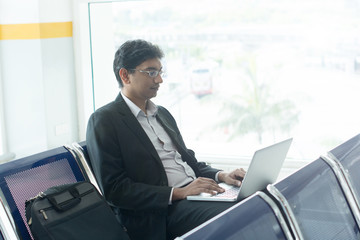 indian male business man working from airport terminal
