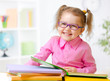 Happy child girl in glasses reading books in room - 75577164