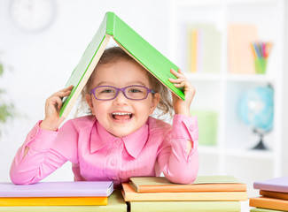 Happy kid in glasses under roof made from book