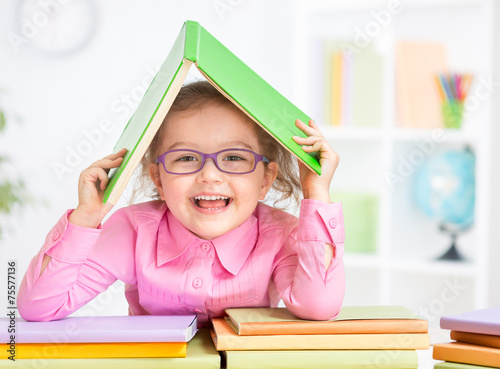 Happy kid in glasses under roof made from book - 75577136
