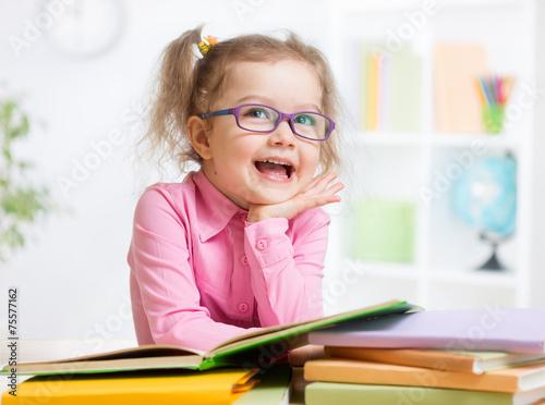Leinwanddruck Bild Happy kid reading books and dreaming