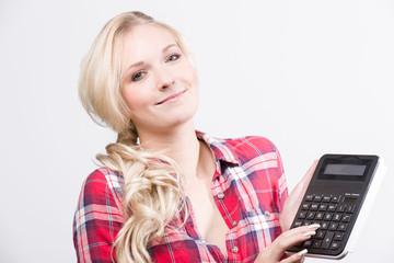 Junge Frau lächelt mit Taschenrechner