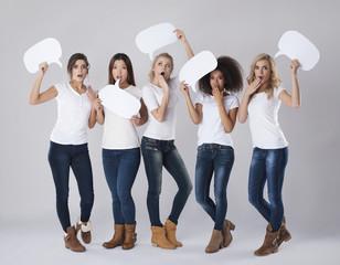 Shocked girls holding empty speech bubbles above heads