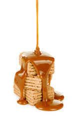 sweet caramel sauce is poured on a waffle cookies