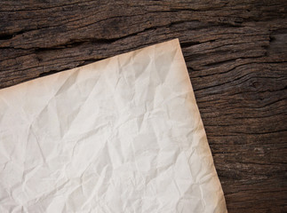crumpled old paper on wooden plate