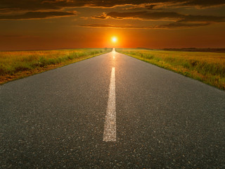Open, straight asphalt road at sunset
