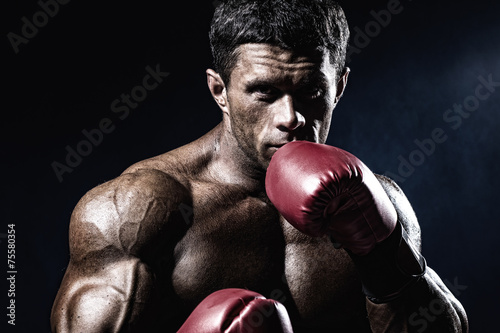 Foto op Aluminium Vechtsport Strong muscular boxer in red boxing gloves. A man in a boxing st
