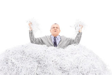 Desperate senior holding a bunch of shredded paper