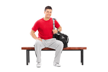 Male sportsman sitting on a wooden bench