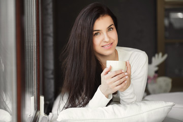 Portrait of a young woman by the window with a cup of coffee.