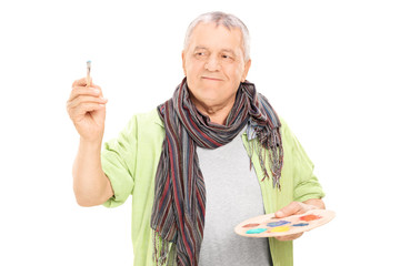 Mature painter holding paintbrush and color pallet