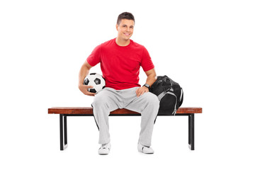 Young football player sitting on a bench