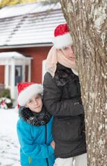 Junge Frau und ihr kleiner Sohn mit Weihnachtsmützen