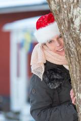 Attraktive junge Frau mit weihnachtsmütze vor rotem Schwedenhaus