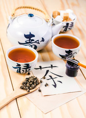 """Chinese hieroglyph for """"tea"""" and set of tea"""