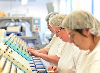 Arbeiterinen verpacken Pralinen in einer Fabrik