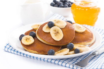pancakes with banana, honey and blueberries, isolated