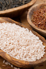 pink unpolished rice in a wooden bowl, top view