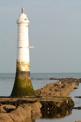 Small white lighthouse on rocks