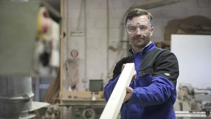 Carpenter with security glasses working on wood