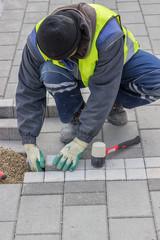 Construction worker installing sidewalk pavement